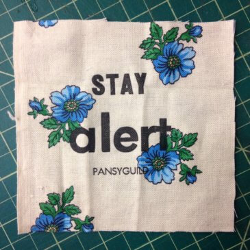 "white cloth with blue flowers printed and ""stay alert"" written in the middle in print"